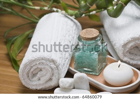 Spa background with bath salts, a towel, a candle and bamboo plants.