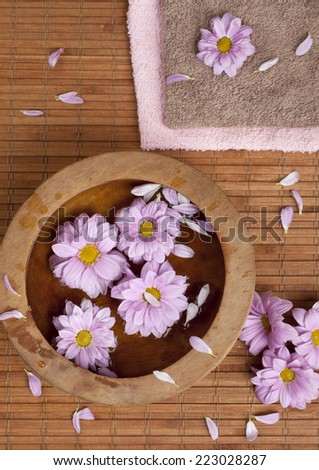 Spa background with beautiful pink blossoms in a wooden bowl.