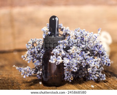 Spa background with bunch of lavender and glass vial with essential oil. - stock photo