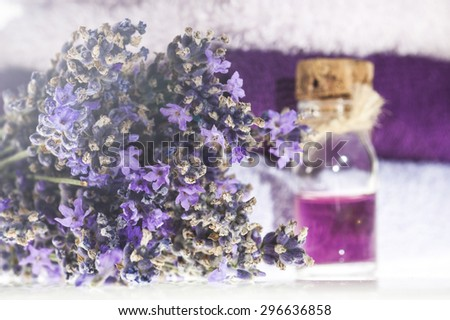 Spa background with bunch of lavender, towel and bottle with aromatherapy oil on a white background. - stock photo