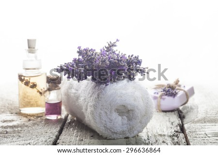 Spa background with bunch of lavender, towel and bottles with aromatherapy oil on a white wooden background. - stock photo