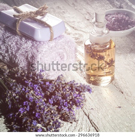 Spa background with bunch of lavender, towel and bottles with aromatherapy oil on a white wooden background. With special blurred effect. - stock photo