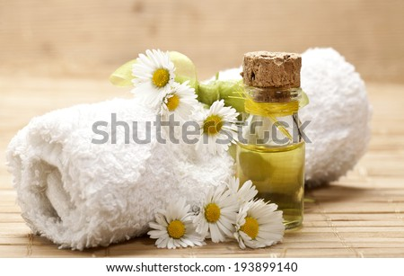 Spa background with glass vial with essential oil, rolled towel and chamomile on wooden background.  - stock photo