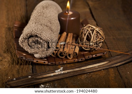 Spa background with rolled towel, candle, sticks of cinnamon and incense stick. - stock photo