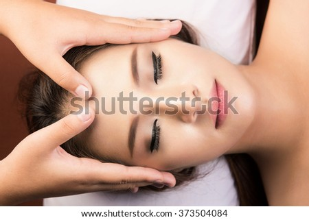 spa,beauty and health concept - beautiful woman in spa salon getting face treatment - stock photo