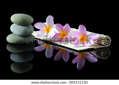 Spa, beauty and wellness concept - Stacked Zen stones Frangipani flowers on a bamboo mat with reflection, dark background.  - stock photo