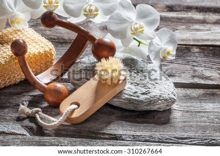 spa beauty treatment concept - symbols of massage, washing-up and nail care for indulging yourself set on old wood, gray texture stone and white orchid flower background for genuine body care decor - stock photo