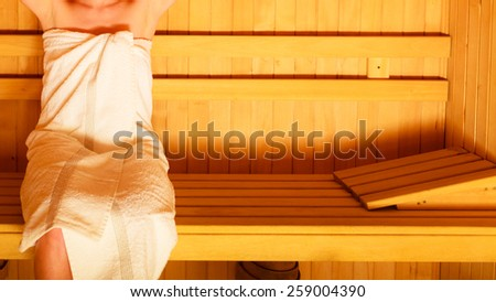 Spa beauty well being and relax concept. Woman body white towel, girl sitting relaxed in wooden sauna - stock photo