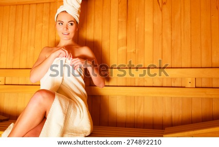 Spa beauty well being and relax concept. Woman white towel sitting relaxed in wooden sauna - stock photo