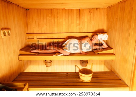 Spa beauty well being and resort concept. Woman in full length white towel lying relaxed in wooden finnish sauna - stock photo