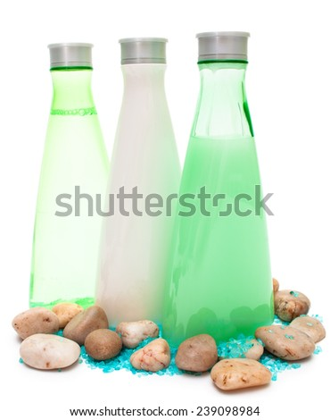 Spa bottles (green and white) with small stones and sea salt isolated copy space - stock photo