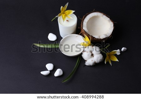 Spa coconut products. Coconut oil on table with flower, candle and white stones - stock photo