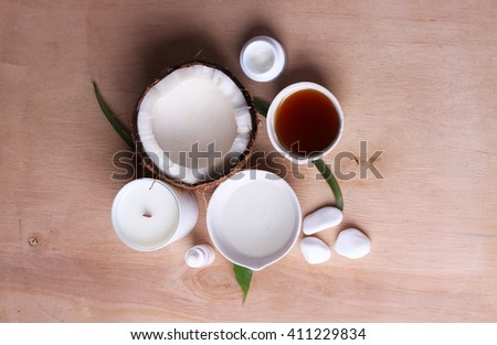 Spa coconut products. Coconut oil on table with flower, candle and white stones on wooden background - stock photo