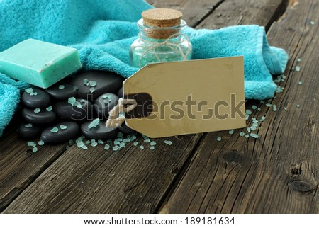 spa composition of stones, towel, and bottle on old wooden boards