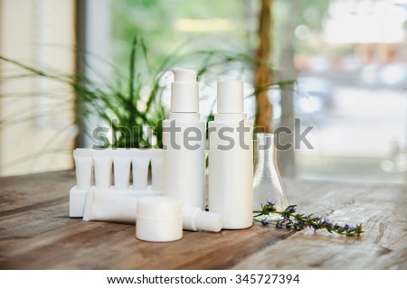 SPA composition. Set of copyspace cosmetic bottles and tubes. Face/body care concept: bottles of creams/lotions/serums. Selective focus, sallow DOF, close up.  - stock photo