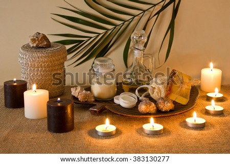 Spa composition with candles. Massage oil and cream, comb, soap, sponges and various hygiene products