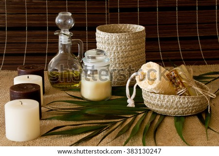 Spa composition with candles. Massage oil and cream, soap, sponges and various hygiene products