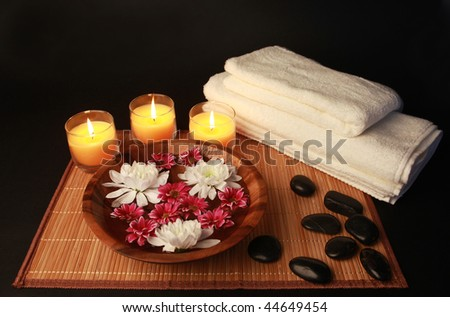 spa composition with flowers towels stones and candles