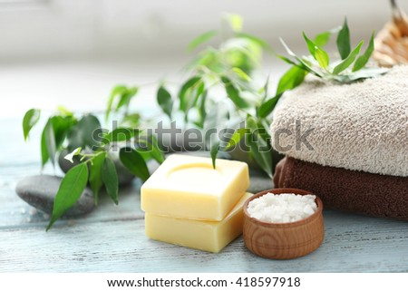 Spa composition with green leaves on wooden background