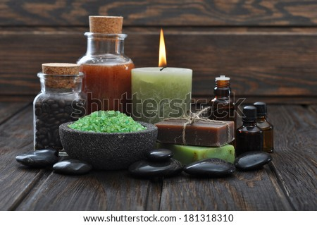Spa composition with green sea salt and massaging stones on wooden background