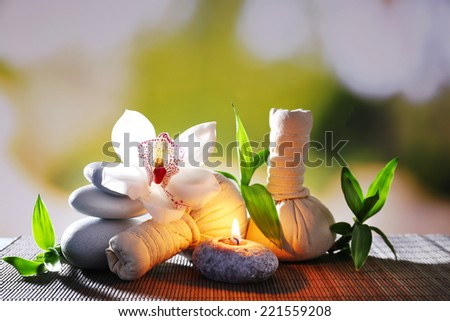 Spa composition with herbal massage bags, candle and bamboo on table on natural background - stock photo