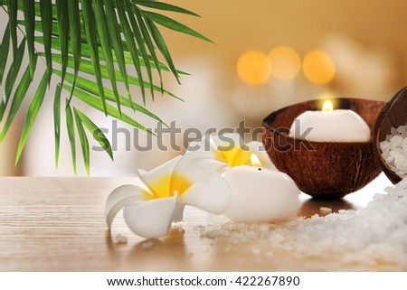 Spa composition with plumeria, coconut and sea salt on natural blurred background - stock photo