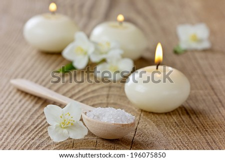 Spa composition with sea salt bath in wooden spoon, jasmine flowers and burning candles on a rustic surface, aromatherapy concept, selective focus - stock photo