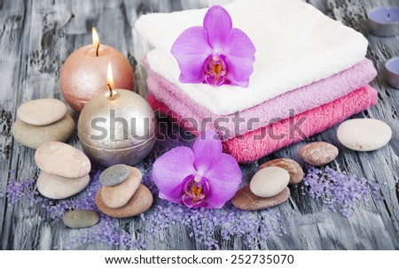 Spa composition with  spa accessories, orchid flowers and towels on a wooden background - stock photo