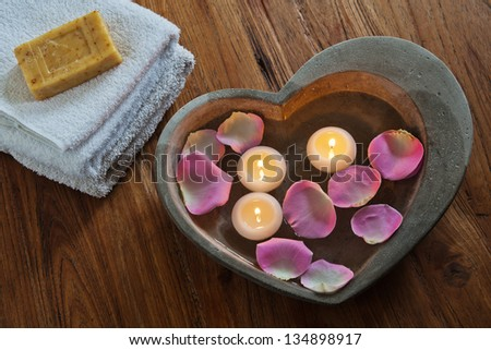 spa composition with stone heart filled with water rose petals and floating candles