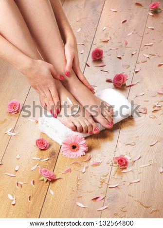 Spa compositions of sexy female legs and plenty of different petals  and flowers - stock photo