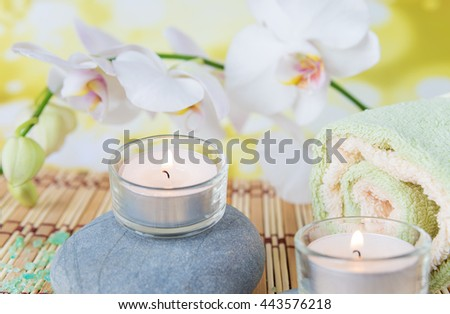 Spa concept: bath towels, two lighted candles on a wild rock and a branch of white orchid - stock photo