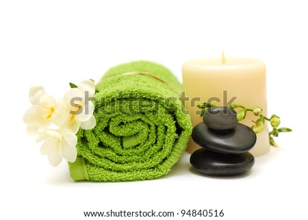 Spa concept - black stones, white flower, green towel - stock photo