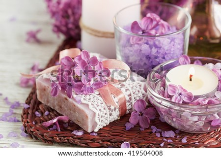 SPA concept: composition of spa treatment with natural sea salt,  aromatic oil and lilac flowers on white wooden background - stock photo