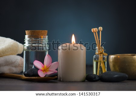 Spa concept in dark background with ambient lights , cold stones and frangipani