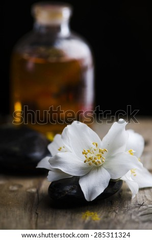 Spa concept. Jasmin flower and scented oil on wooden table. - stock photo