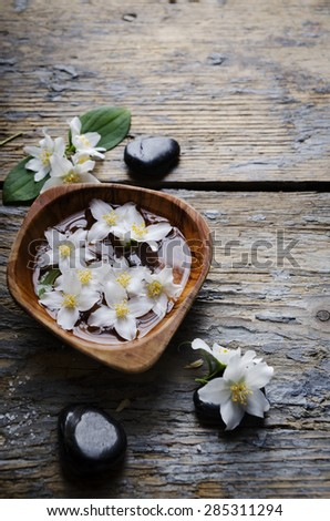 Spa concept. Jasmin flower and spa stones on wooden table. - stock photo