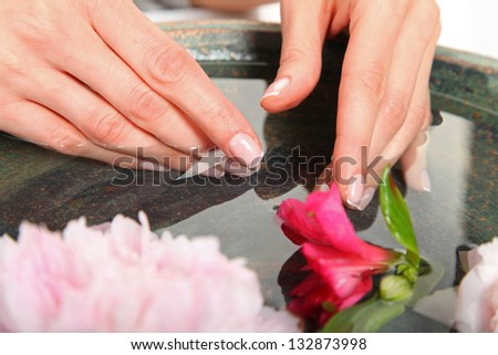 Spa Concept  - manicure, water and flowers - stock photo