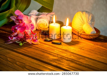 spa concept of pink orchid flower, thai herbal compress balls in basket, towels, zen stones and candles on wooden background - stock photo