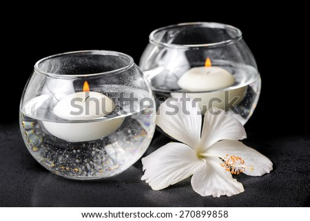 spa concept of white hibiscus flower and candles in vase with water - stock photo