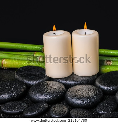 spa concept of zen basalt stones, candles and natural bamboo with dew, closeup  - stock photo