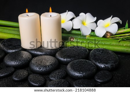 spa concept of zen basalt stones, three white flower frangipani, candles and natural bamboo with drops - stock photo