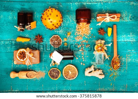 spa concept on wooden background: Aromatic oils, salt, soap, citrus, cinnamon candles. top view - stock photo