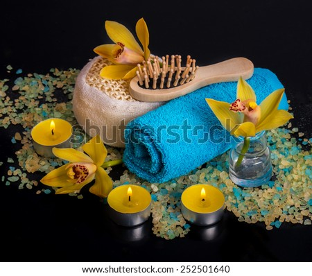 Spa concept. Orchid flowers, sea salt, candles and objects for spa procedures on a black background - stock photo