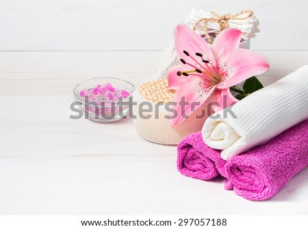 Spa concept. Pink lily flower,sea salt,towels and objects for spa procedures on a white wooden background. - stock photo
