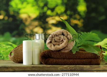 spa concept - towels and body cream on natural green background - stock photo