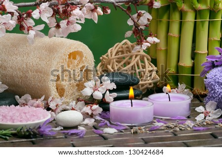Spa concept with aromatic candles, cotton towels, loofah, bath salt and healing pebbles