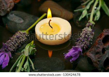 Spa concept with aromatic candles, lavender, healing pebbles and water - stock photo