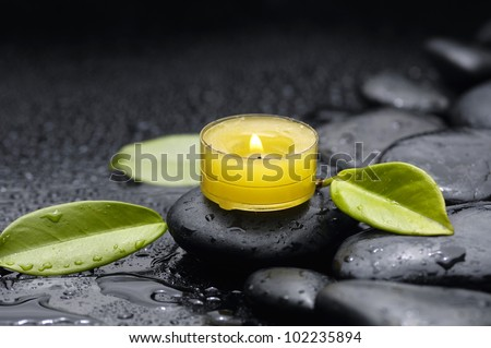 spa concept with candle and zen stones and green leaf on zen stones