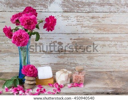 Spa concept with coconut soap,salt,zen stone and beautiful rose flowers on grunge wooden background  - stock photo