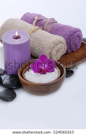spa concept with orchid salt in bowl, towel, candle